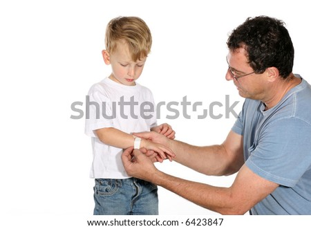 Handsome father putting a band aid on his son's arm