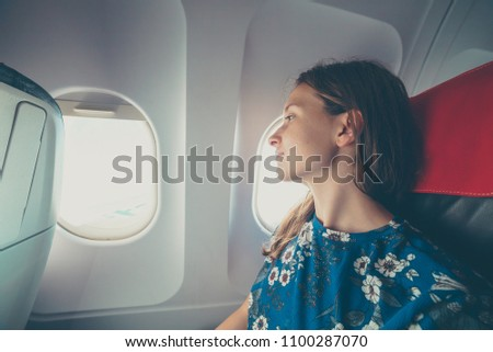 handsome female airplane passenger enjoying the view from the cabin window during flight