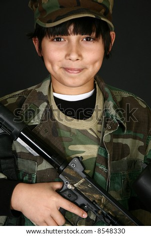 Handsome Filipino 11 year old boy in camo with paintball rifle ...