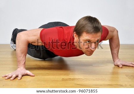 Handsome fit man pursuing a healthy lifestyle, doing push-up fitness exercise in the gym