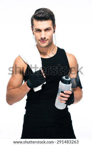Handsome fitness man holding towel and bottle with water isolated on a white background. Looking at camera #291483263