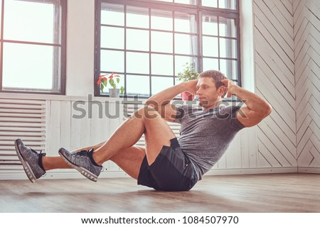 Handsome fitness man in a t-shirt and shorts doing abdominal exercises on floor at home.