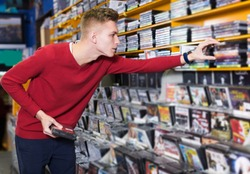 Handsome focused man looking for interesting movies on shelves of CD shop