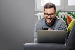 Handsome freelancer working from home, lying on his stomach on the couch with laptop and phone. Smiling. Wearing glasses. Copy space.