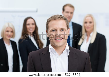 Handsome friendly young manager or team leader with a confident smile posing in front of his team with shallow dof