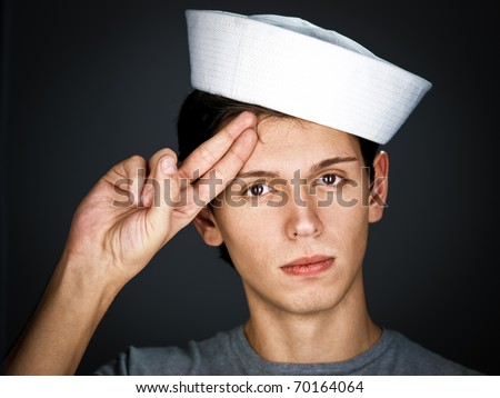 handsome  gallant  young man in the sailor  cap is saluting