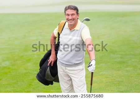 Handsome golfer standing with golf bag on a foggy day at the golf course
