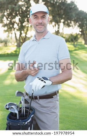 Handsome golfer standing with golf bag on a sunny day at the golf course