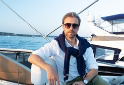 Handsome good looking mature man on the yacht. Portrait of successful man on sailing boat at sunset.