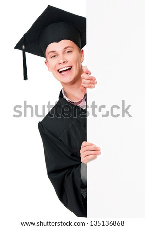 Handsome graduate guy student in mantle showing blank placard board, isolated on white background