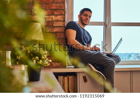 Handsome greek student holds the laptop while sitting on a window sill in student dormitory.