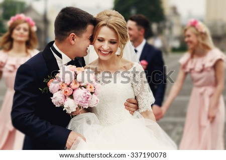 Handsome groom in suit hugging elegant blonde bride with bridesmaids and groomsmen