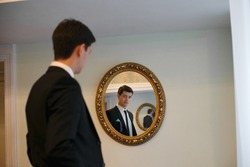Handsome groom is watching in the mirror