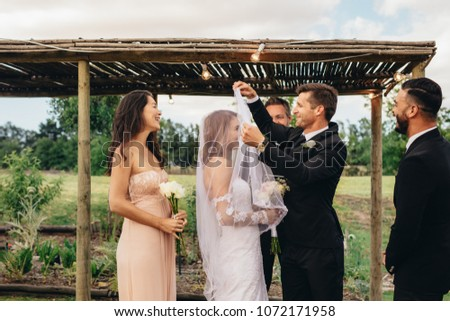 Handsome groom lifting up bridal veil to kiss beautiful bride. Couple having an outdoor wedding ceremony. Bride and groom about to kiss after the wedding ceremony ストックフォト ©