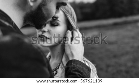 Stock Photo Handsome guy and blonde girl walking on the grass near the river and forest. man gently embraces girl, stroking his face and kisses
