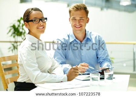 Handsome guy and his pretty colleague looking at camera while solving some business matters