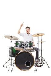 Handsome guy behind the drum kit on a white background in shirt and trousers