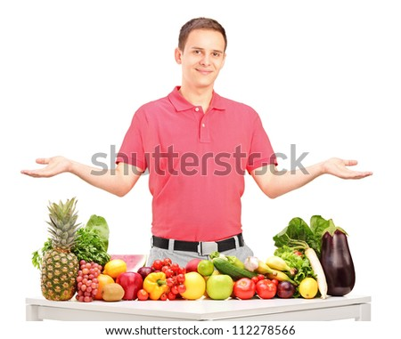 Handsome guy gesturing with his arms behind a table with fruits and vegetables isolated on white background