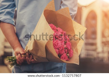 Handsome Guy Holding Flowers Behind His Back and Waiting for Beautiful Girlfriend. Magnificent Bouquet of Pink Roses. Surprised Enamored Girl Pleased with Gift from Her Young Handsome Man. #1132757807