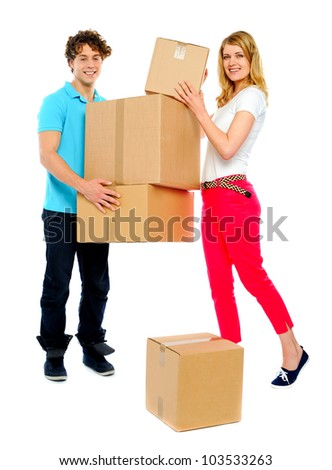 Handsome guy holding stack of cardboard boxes while woman doing the placement