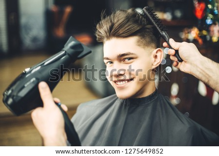 Handsome guy in the barbershop smiling, haircut process. Looking at the camera #1275649852