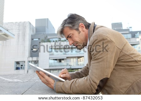 Handsome guy in town using electronic tablet