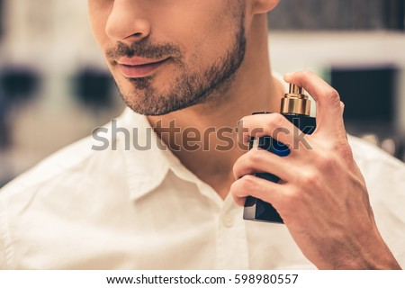 Handsome guy is choosing perfumes and smiling while doing shopping in the mall