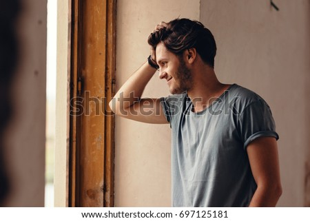 Handsome guy looking pleasant and smiling. Standing near the window of second floor and gazing at group of pretty college girls walking in the road. Caressing long brown hair romantically. #697125181