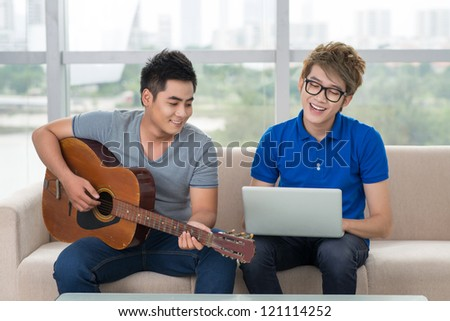 Handsome guy playing the guitar while his friend surfing the internet