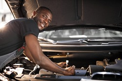 handsome guy repairing auto's hood, using tools. wearing unifrom, concentrated on work