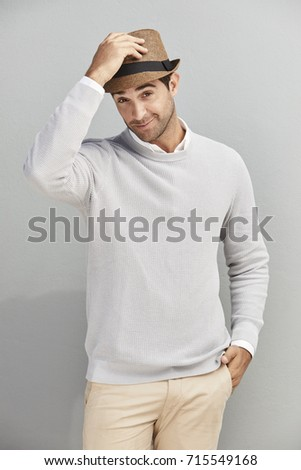 Handsome guy tipping hat to camera, portrait