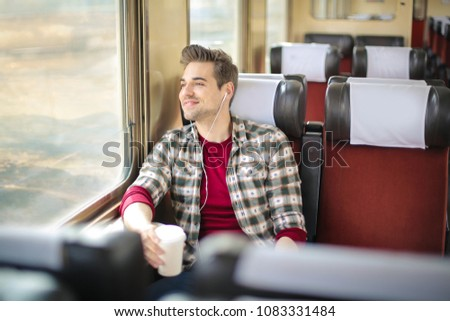 Handsome guy traveling on a train, looking out of the window