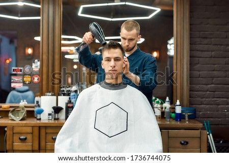 Handsome guy visiting barbershop. Young man sitting in barbershop chair while male barber drying his hair. Getting new haircut at barbershop. Hairstyle. Mens haircut. Beauty salon