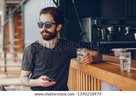 Handsome guy with a tattoo.The guy in the cafe. Man in glasses