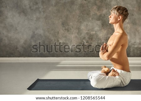 Handsome guy with naked torso sitting cross legged in lotus pose on mat, practicing meditation after asanas, pressing hands together and closing eyes, being thankful and peaceful. Yoga and meditation #1208565544