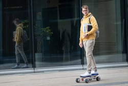 Handsome guy, young man, hipster, student or pupil in glasses on his face riding on electric urban modern skateboard with backpack, books and textbooks. Eco transport, technology concept.