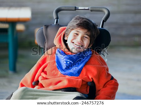 Handsome, happy biracial eight year old boy smiling in wheelchair outdoors Stock photo ©