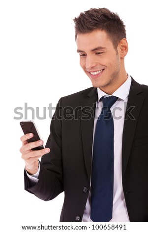 Handsome happy business man reading an SMS on smartphone against white background