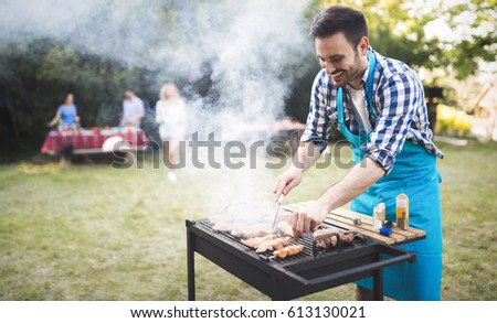 Handsome  happy male preparing barbecue outdoors for friends