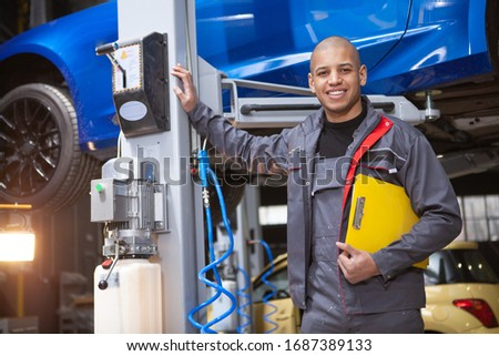 Handsome happy mechanic smiling to the camera while working at car service station Stock photo ©