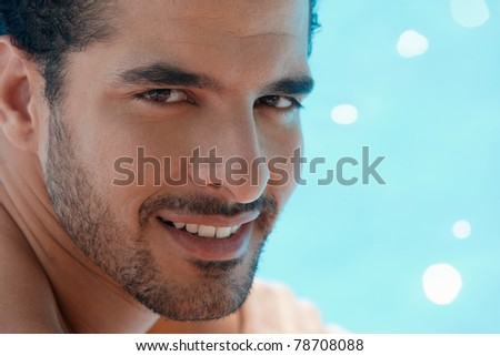 Handsome happy young hispanic man smiling and relaxing near hotel pool. Horizontal shape, headshot, copy space