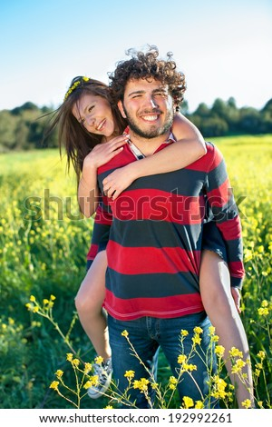 Handsome happy young man giving his pretty girlfriend a piggy back ride through a field of colorful yellow rapeseed flowers on a warm sunny summer day.