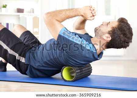 Handsome Healthy Guy Doing an Exercise on a Mat with Foam Roller on his Upper Back