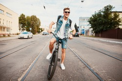 Handsome hipster enjoying city ride by bicycle