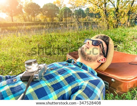 Handsome hipster guy relaxing with old fashioned camera on meadow - Nature concept with young man sleeping in the park - Warm vintage filtered look