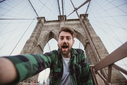 Handsome hipster guy taking selfie self-portrait on Brooklyn Bridge, New York. Cute bearded student takes funny picture for travel blog.