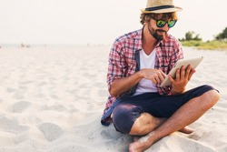 Handsome  hipster  man    with   beard in straw hat, checkered shirt, stylish  sunglasses sitting on white sand on  amazing summer beach  and using tablet , warm  sunlight, soft toned image.