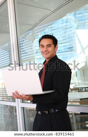 Handsome hispanic business man at office with laptop computer
