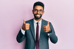 Handsome hispanic business man with beard wearing business suit and tie success sign doing positive gesture with hand, thumbs up smiling and happy. cheerful expression and winner gesture.