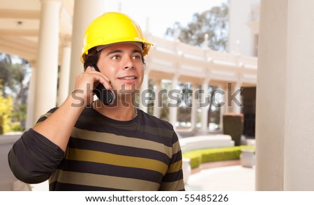 Handsome Hispanic Contractor with Hard Hat Talking on His Cell Phone.